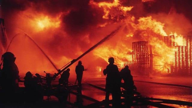 Feuerwehrleute vor brennenden Gebäuden.