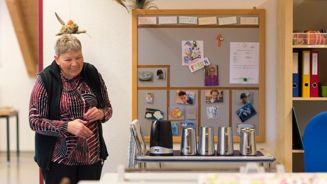 Eine ältere Frau steht in einem Raum neben einem Tisch mit Thermoskannen