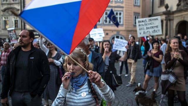 Protestierende mit Spruchbänden und Fahnen.