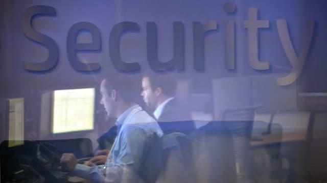 Männer vor Computer-Bildschirmen, gespiegelt in einem Glas.