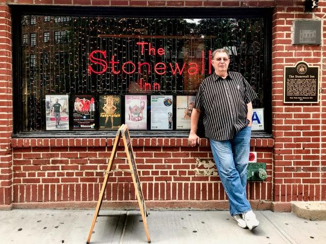 """Ein Mann mit gestreiftem Hemd und Jeans steht vor einer Bar. Im Schaufenster ist eine rote Leuchtschrift """"The Stonewall Inn""""."""