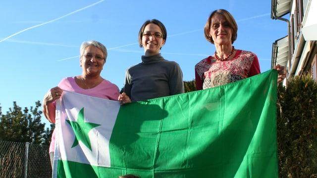 Bildlegende: Barbara Pochanke (links), ihre Tochter Veronika und Enkelin Elina sowie Verena Chaves-Walder (rechts): Die grüne Farbe der Esperanto-Fahne steht für Hoffnung.