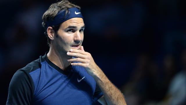 Roger Federer blickt mit der Hand am Kinn nachdenklich ins Publikum.
