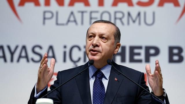 Der türkische Präsident Erdogan spricht in zwei Mikrofone.