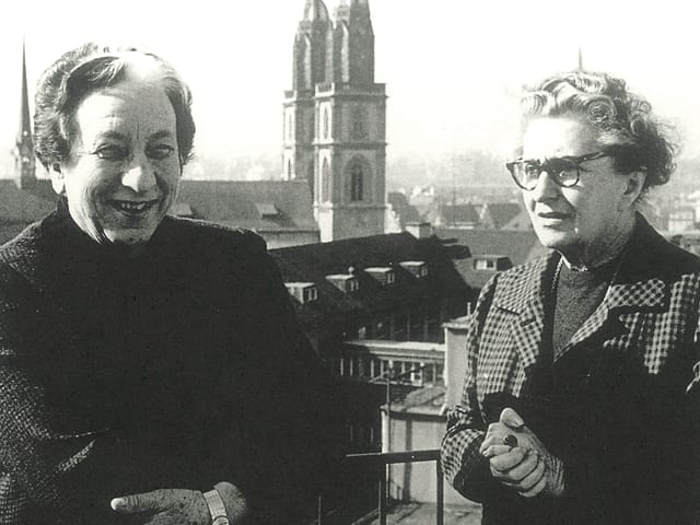 Marguerite Steiger und Hermine Raths auf einem Schwarzweiss-Foto mit dem Zürcher Fraumünster im Hintergrund.