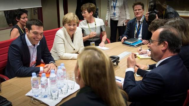 Verschiedene Spitzenpolitiker sitzen an einem Tisch mit Tsipras und scherzen.