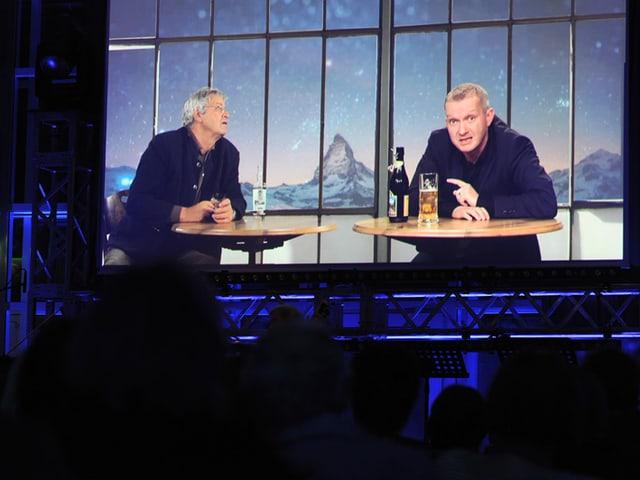 Bühne mit Bildschirm - Videoeinspieler von Gerhard Polt und Simon Enzler