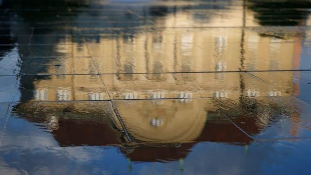 Der Sitz der Schweizerischen Nationalbank spiegelt sich im Wasser.