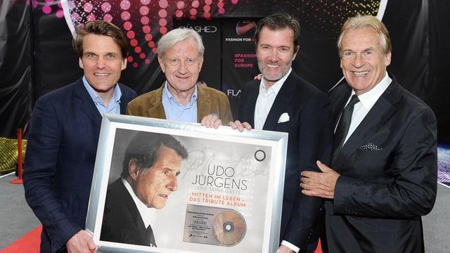 Gruppenfoto mit den vier Männern, die ein Bild mit Foto von Udo Jürgens und veredelter CD halten.