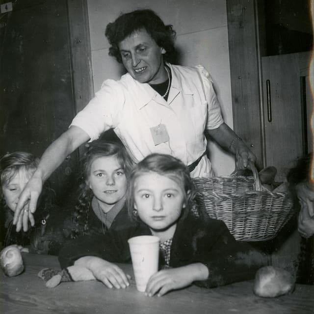 Eine Frau steht hinter Kindern, die an einem Tisch sitzen.