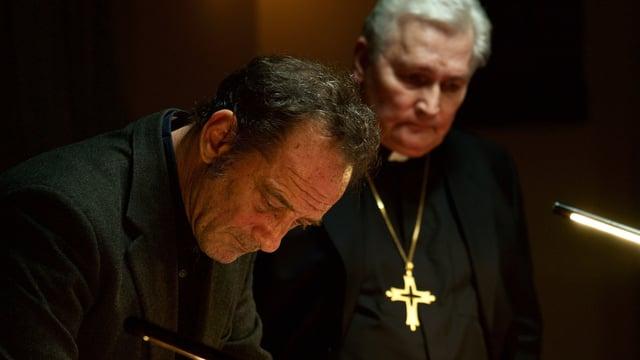 Ein Mann und ein Pfarrer mit goldenem Kreuz um den Hals. Beide in Schwarz gekleidet.