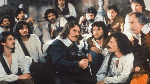 Ein Mann mit einer grossen Nase steht inmitten einer Gruppe von Männern.