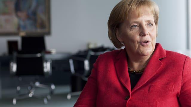 Die Bundeskanzlerin im roten Sakko während eines Interviews im Kanzleramt.