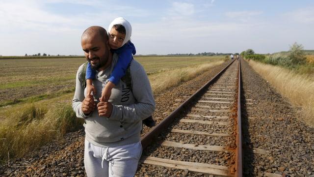 Ein Mann aus Syrien trägt ein kleines Kind auf dem Rücken und wandert über ein Bahngleis bei der ungarisch-serbischen Grenze..