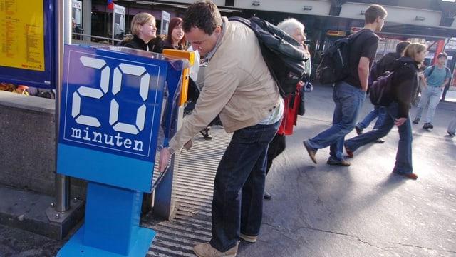 Ein junger Mann schnappt sich eine 20-Minuten-Zeitung aus der blauen Zeitungsbox.