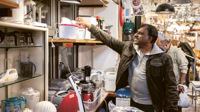 Ein Mann holt ein Elektrogerät vom Regal.