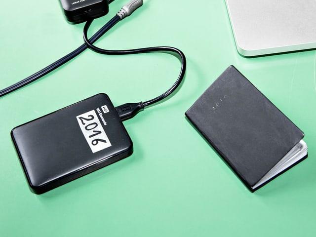 Eine externe Festplatte und ein schwarzes Notizbuch auf grünem Hintergrund.