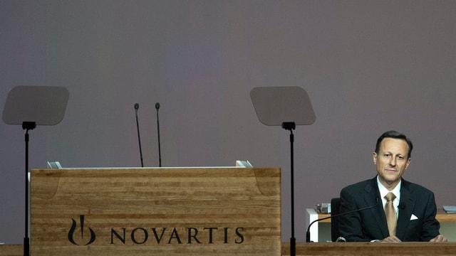 Zu sehen ist ein mit edlen Holzpanelen verkleidetes Rednerpult mit zwei Mikrophonen. Das Rednerpult ist mit dem Schriftzug Novartis angeschrieben. Das Rednerpult ist verwaist. Daneben sitzt Daniel Vasella in Anzug und Kravatte und neutralem Gesichtsausdruck.