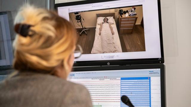 Eine Frau schaut auf einen Bildschirm, auf dem eine schlafende Frau zu sehen ist.