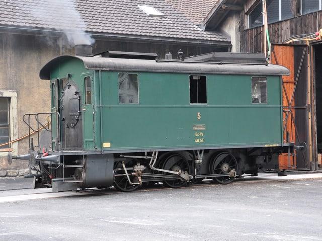 Die Lokomotive steht vor einem Schopf.