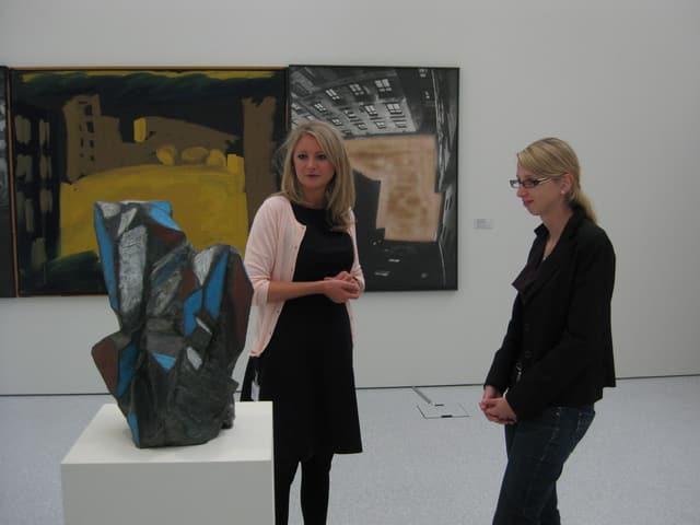 Zwei Frauen stehen vor einem Kunstwerk.