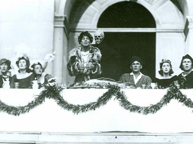 Menschen in Kostümen auf einem Balkon. In der Mitte eine Frau und ein Skelett-Mann.
