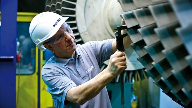 Ein Mann mit Bauhelm, daneben eine Turbine.