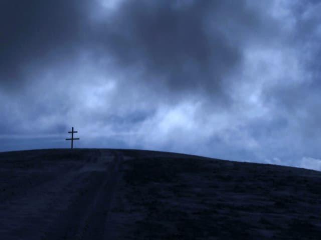 Landschaft bei Escholzmatt im Entlebuch, einer der Schauplätze im Film «Arme Seelen»: Ein Kreuz auf dem Berg, umgeben von dunklen Wolken.