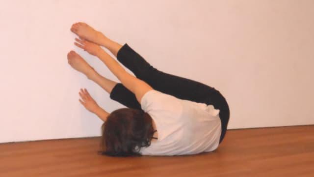 Eine Frau in Gymnastikhose und weissem T-Shirt stemmt sich mit Armen und Beinen gegen eine Wand.