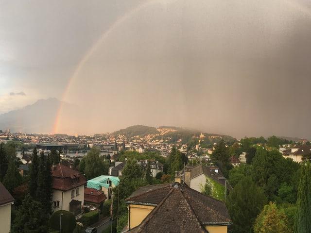 Häuser und Bäume in einer Stadt. Es ist stark bewölkt und ein schwacher Regenbogen erscheint im grauen Regenvorhang.