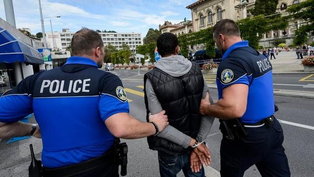 Symbolbild: Ein dunkelhäutiger Mann wird von zwei Polizisten abgeführt.