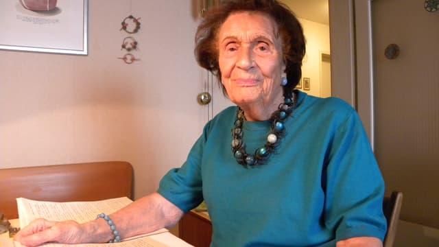Seniorin an Küchentisch mit Papier Buchseiten vor sich liegend.