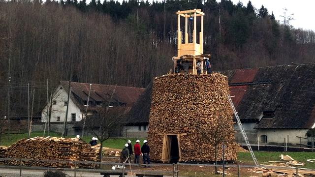 Männer stehen vor dem grossen Berg aus Holz. In der Mitte ragt das Gerüst heraus, das die Endehöhe markiert.