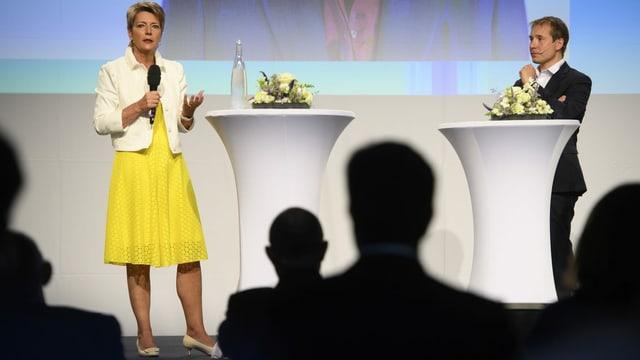 Bundesrätin Karin Keller-Sutter auf der Bühne mit Nationalrat Philippe Nantermod. Sie hält ein Mikrofon.