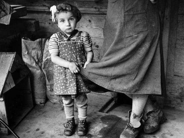 Ein ärmlich gekleidetes Mädchen hält sich an der Schürze einer Frau fest und blickt traurig drein.