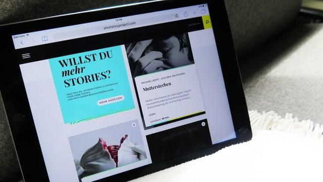 Ein Tablet auf einem Sofa und einer Decke. Auf dem Tablet ist eine Bildschirmaufnahme der Seite «The Short Story Project».