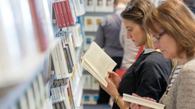 Zwei Frauen stehen lesend an einem Bücherregal