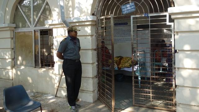 Am Eingang zur geschlossenen Frauenstation der Psychiatrie in Cuttack steht ein kräftiger Wachmann mit einem langen Holzknüppel.