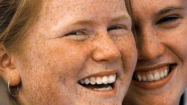 Zwei Mädchen mit ganz vielen Sommersprossen lachen in die Kamera.