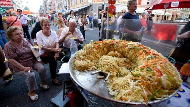 Paella-Pfanne und Leute sitzend drumrum