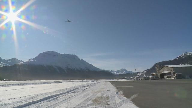 """Vista sin la plazza aviatica - da la vart l'edifizi da l'Airport, davant la muntogna """"La Margna"""" ed en il tschiel blau in aviun ch'è gista partì."""