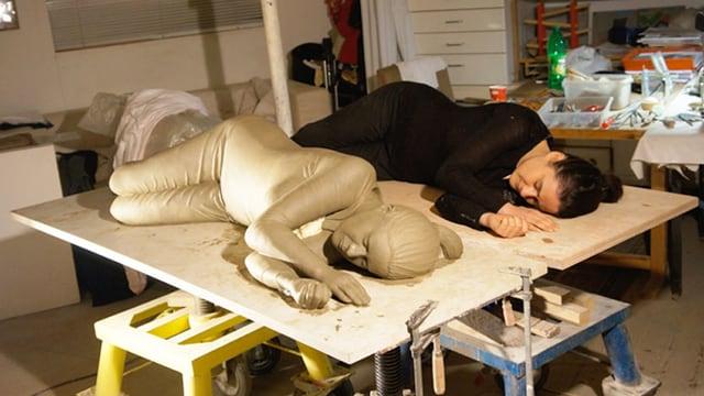 Man sieht Luzia Hürzeler, die neben ihrer Skulptur liegt.