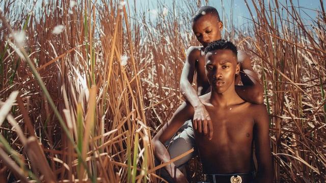 Zwei junge, dunkelhäutige Männer mit nacktem Oberkörper in einem Feld.