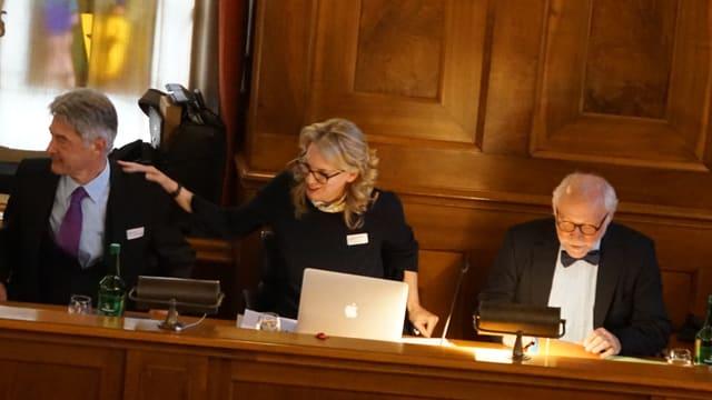 Drei Personen sitzen im Parlament. In der Mitte eine Frau, die nach erfolgter Wahl aufsteht.