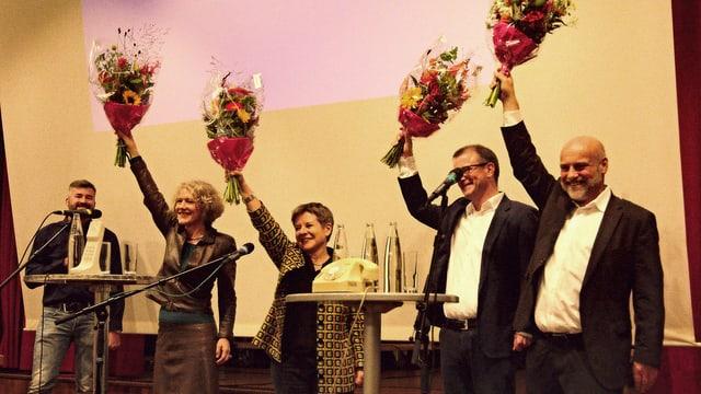 vier KandidatInnen auf Bühne strecken Blumensträusse in die Luft