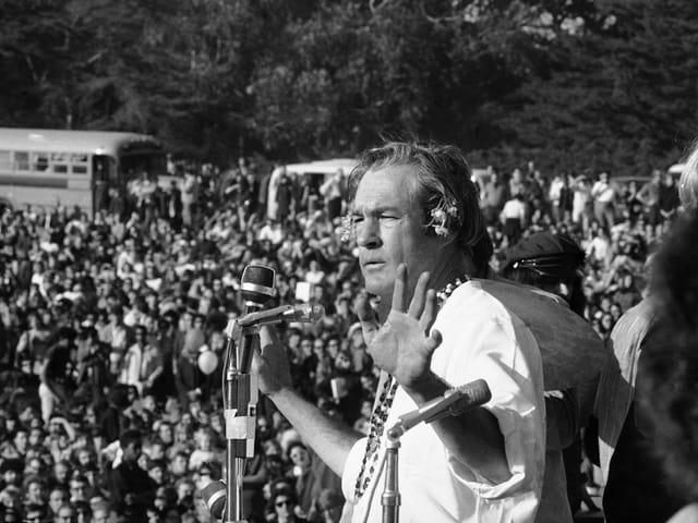 Ein Mann spricht vor einem Mikrophon zu einer Menschenmenge.
