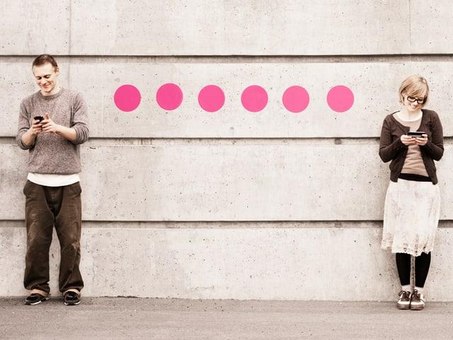 Ein Mann und eine Frau stehen an einer Wand und schauen jeweils auf einen Bildschirm. Eine Linie aus rosa Punkten verbindet ihre Körper.