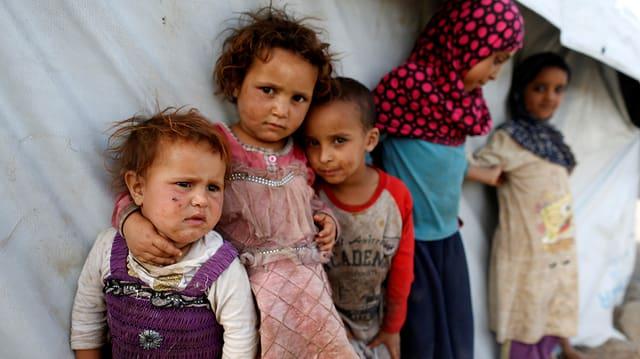 Purtret d'intgins uffants en in champ per fugitivs en il Jemen.