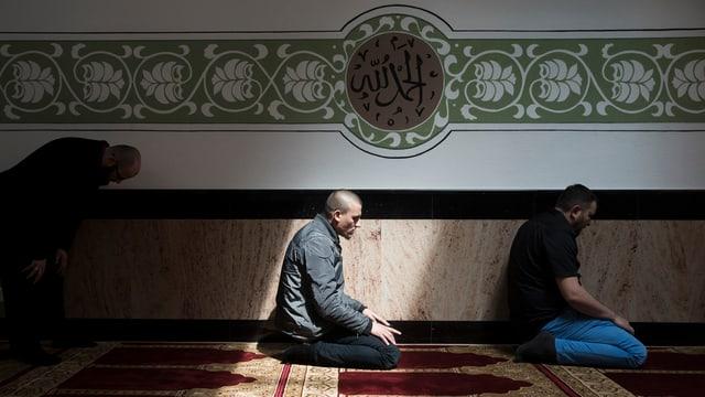 Zwei Männer sitzen auf Teppich und beten