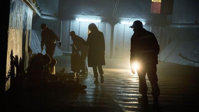 Ein dunkler Raum, in dem mehrere Personen sichtbar sind. Eine Person hält eine Taschenlampe in der Hand.